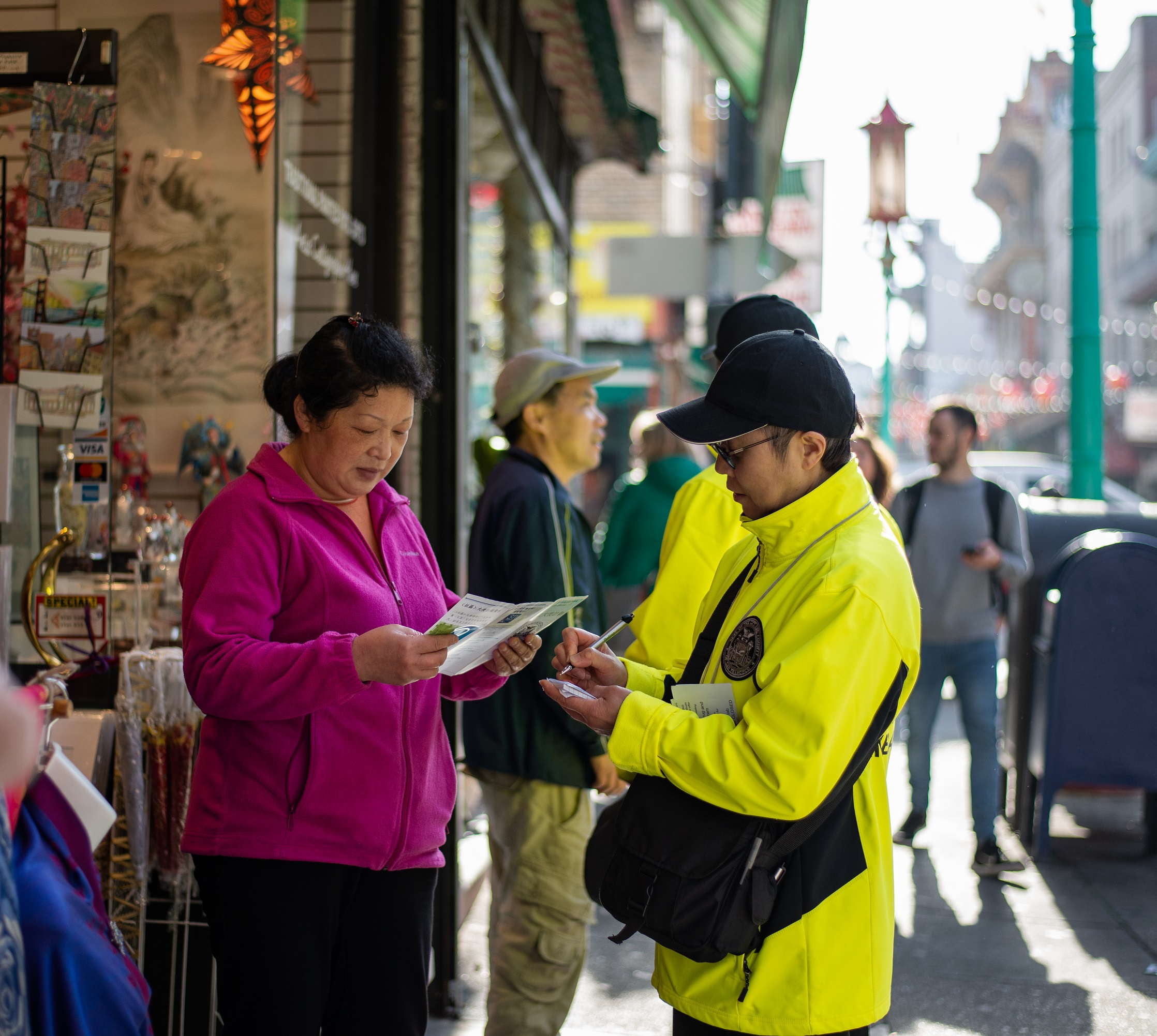 A Community Ambassadors providers information to a store owner in Chinatown