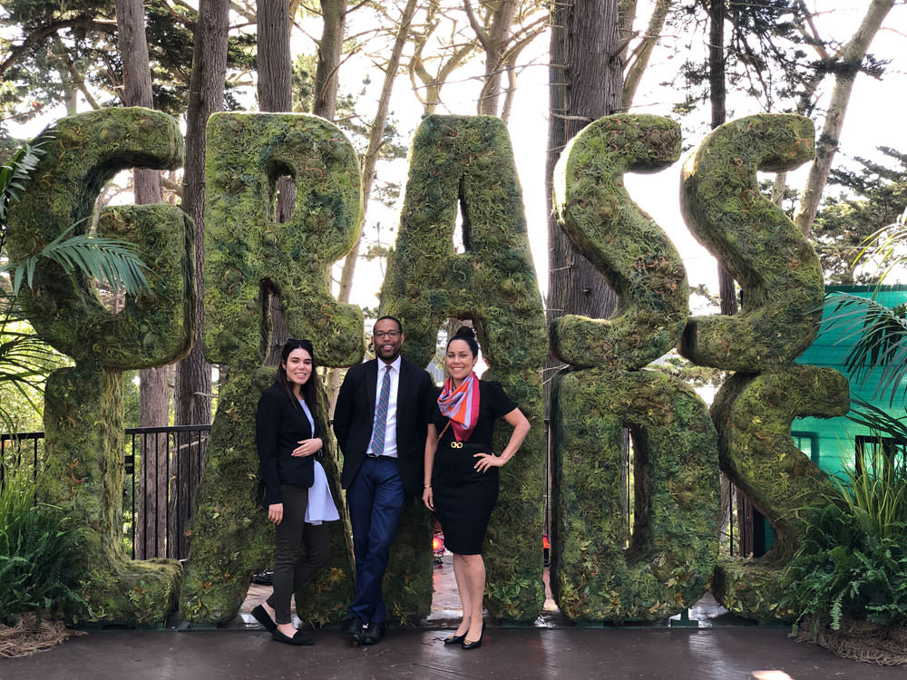 Office of Cannabis staff take a picture in front of the larger than life Grass Lands grass sign.