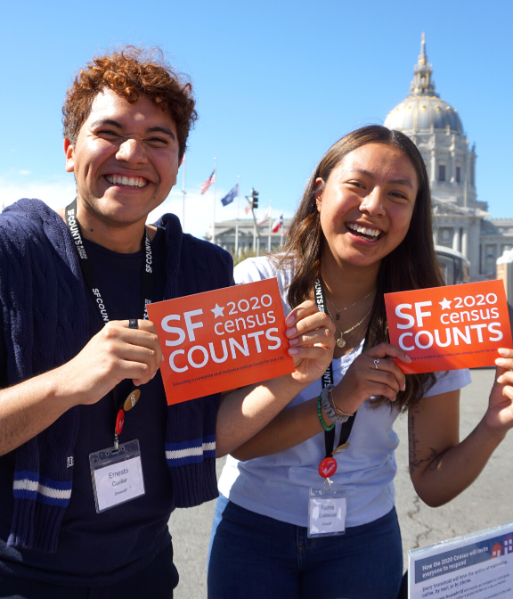 Two young adults holding SF Counts 2020 Census postcards outside of city hall