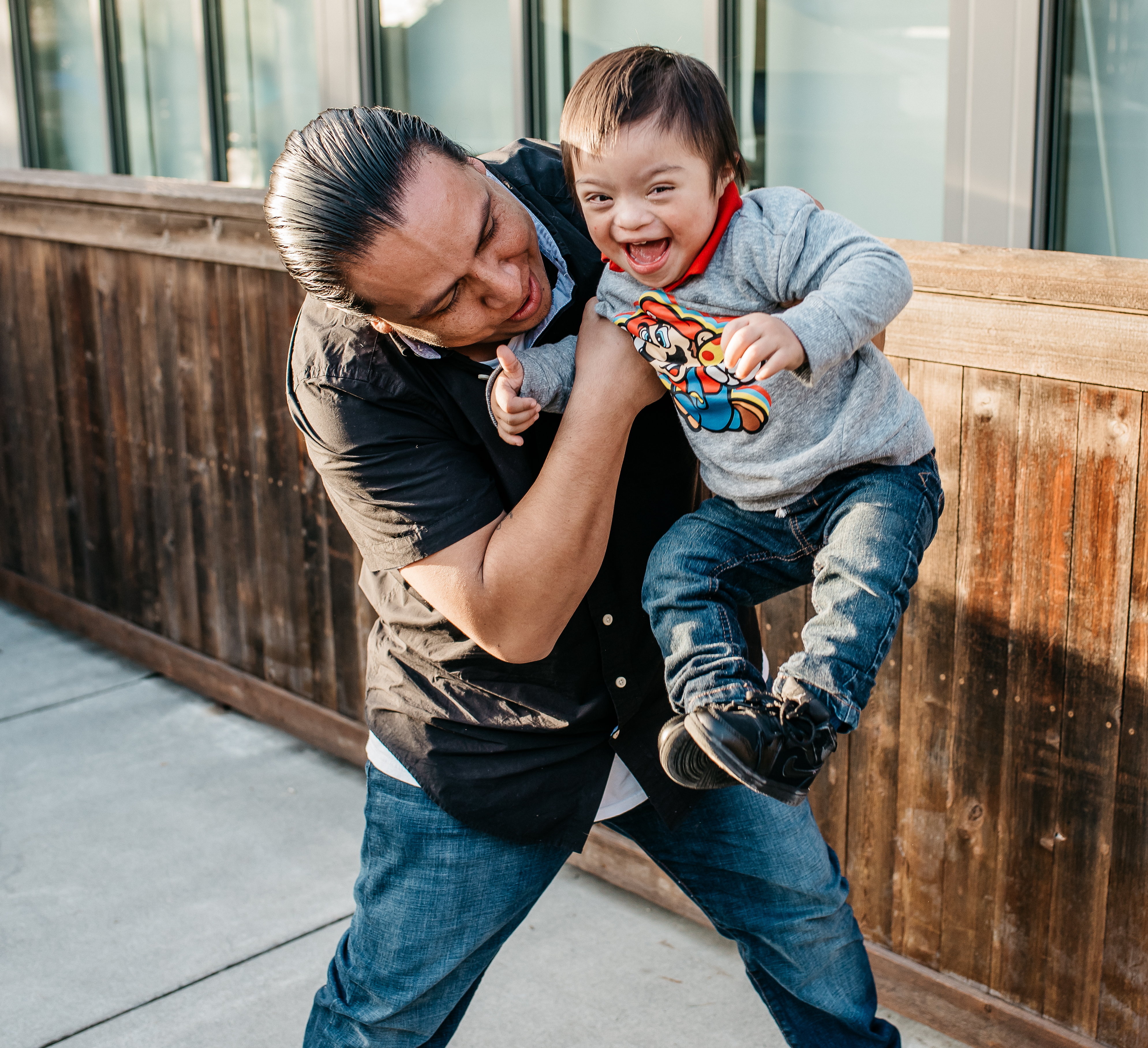Man holding toddler in the air who is smiling
