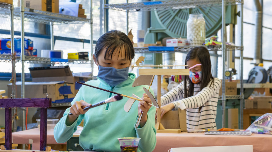 Girls wearing masks work on an art project, sitting at separate tables.