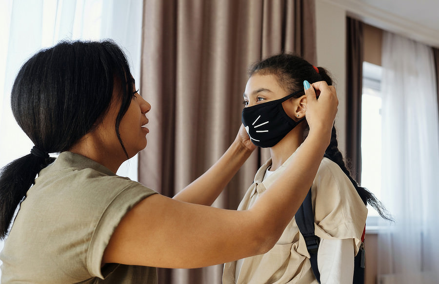 A mother puts a mask on her young daughter.