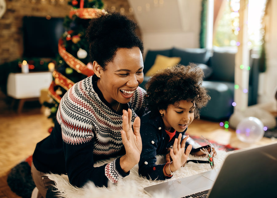 Cheerful Black mother and daughter greeting someone during video call on Christmas.