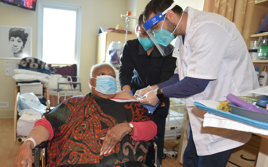 Geraldine McCowan (Mama G) looks up at her healthcare providers as they give her the shot.