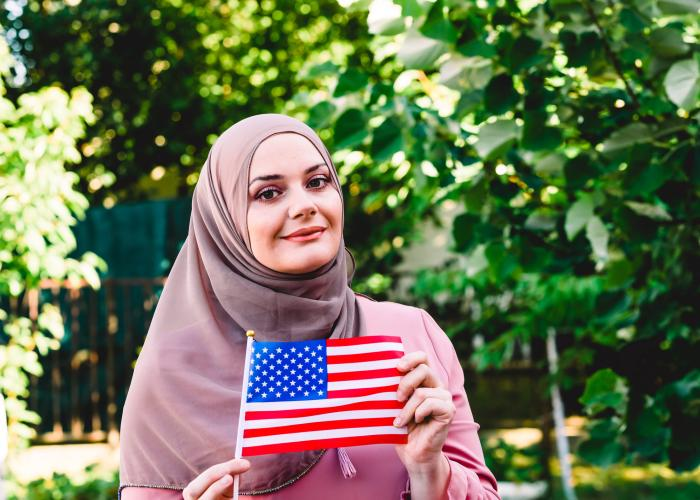 New U.S. citizen holds flag and smiles