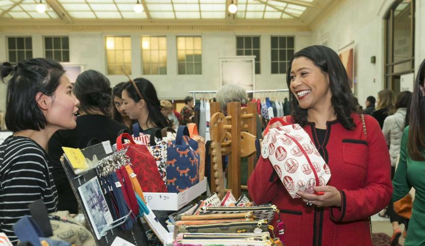 Mayor London Breed at a local market smiling at a vendor while holding an object. Credit: Chamber of Commerce